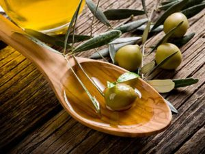 Olive oil poor over wood spoon with olives